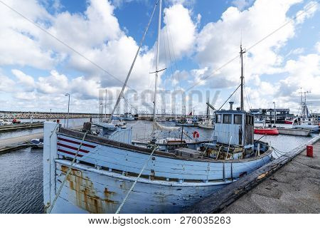 Old Traditional Fishing Boat In A Scandinavian Harbor Under A Cloudy Blue Sky