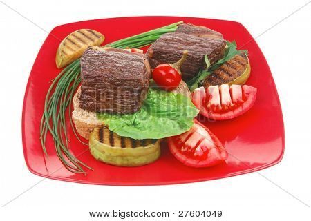 meat savory : beef roasted and garnished with baked apples, raw tomatoes, green chives and pepper, over bread slice on red plate isolated over white background