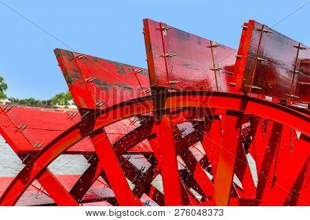 Red Riverboat Paddle Wheel In A River With Trees