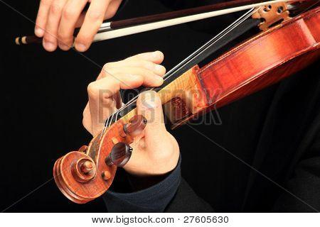 Violin player close up on black