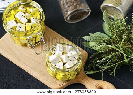 Marinated Feta In A Glass Jar And Spices On A Black Background.