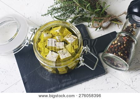 Marinated Feta In A Glass Jar And Spices Against White Background.