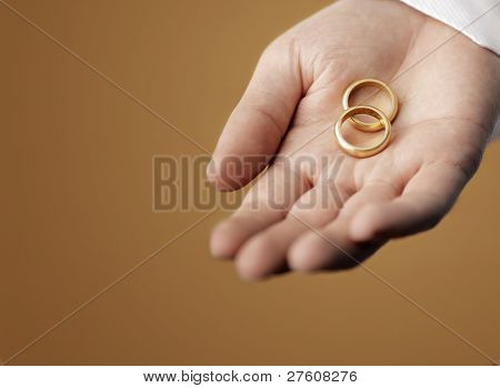 Man holding 100 year old gold wedding rings in his hand.