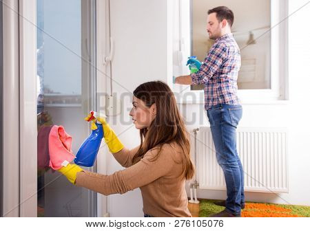 Man And Wife Cleaning Windows With Cloth And Spray Bottle At Home