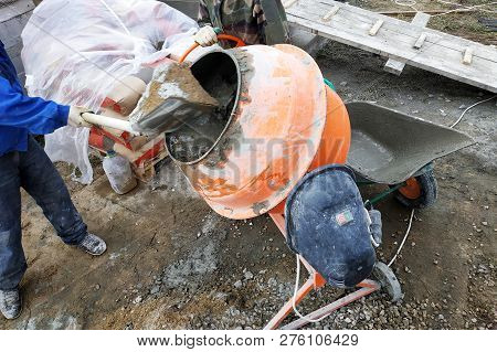 Auxiliary Worker Develops A Cement Mortar In A Concrete Mixer At The Construction Of A Country House
