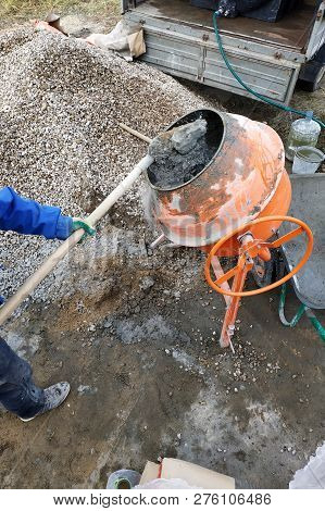 auxiliary worker uses a shovel to prepare a cement mortar on a construction site poster
