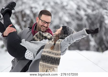 Happy Smiling Couple Enjoying On Snow In Forest. Man Lifting Girl In Front Of White Trees