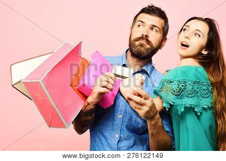 Shopping And Leisure Concept. Couple In Love Holds Shopping Bags On Pink Background. Man With Beard