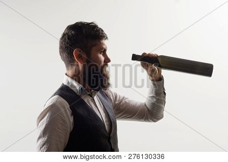 Bearded Man Looks At Bottom Of Bottle. Serious Man Looking Through Wine Bottle. Businessman Looking