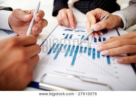Image of human hands with pens over business document at meeting