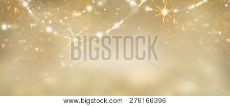Christmas Gold glowing Background. Golden Holiday Abstract Glitter Defocused Backdrop With Blinking Stars and garlands. Tinsel Blurred gold Bokeh on black background. Festive defocused elegant border