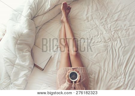 Close Up Legs Women On White Bed. Women Reading Book And Drinking Coffee In Morning Relax Mood In Wi