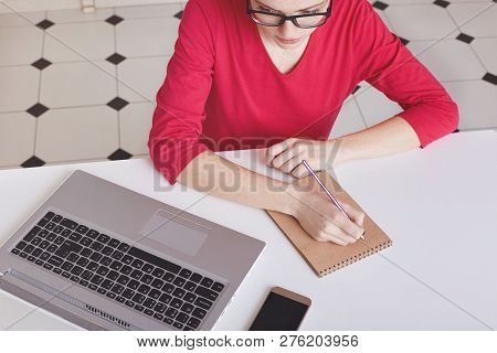 Cropped Top View Of Busy Female Writer Makes Notes In Spiral Notepad, Wears Transparent Glasses And