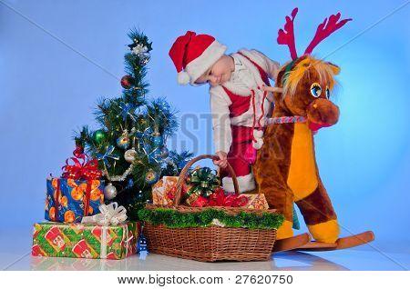 Santa's Little Helper. An adorable baby Santa on his reindeer near the Christmas tree. A boy holds a