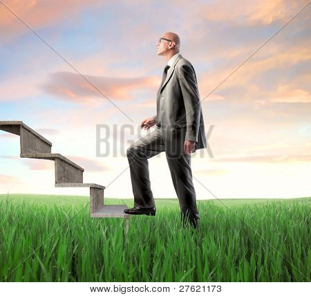 Businessman stepping up a stairway from a green meadow