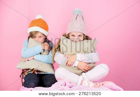 Siblings Wear Winter Warm Hats Sit On Pink Background. Children Boy And Girl Warm Up With Pillows An