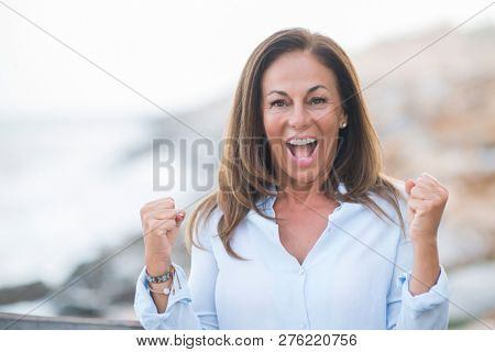 Beautiful middle age hispanic woman at the sea shore on a sunny day screaming proud and celebrating victory and success very excited, cheering emotion