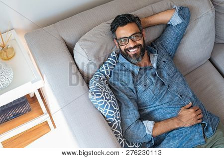 Happy mature man with eyewear and beard relaxing on sofa at home. Handsome latin man with hands behind head. High angle view of cheerful indian man in casual lying on gray couch and looking at camera.