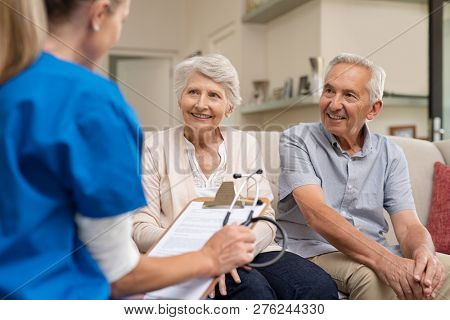 Nurse during home visit with senior couple. Doctor holding clipboard and stethoscope in conversation with old couple at home. Nurse bringing home the results of medical exams.
