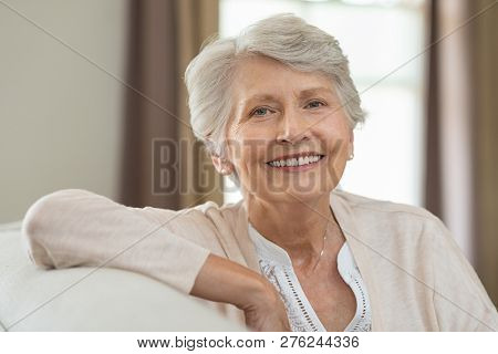 Smiling senior woman relaxing on couch at home and looking at camera. Portrait of elderly woman sitting on sofa. Closeup of cheerful grandmother relaxing indoor.