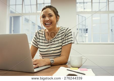 Laughing latin woman using laptop sitting on desk at office. Beautiful student finishing college assignments using computer in a library. Happy casual girl working on laptop and looking at camera.