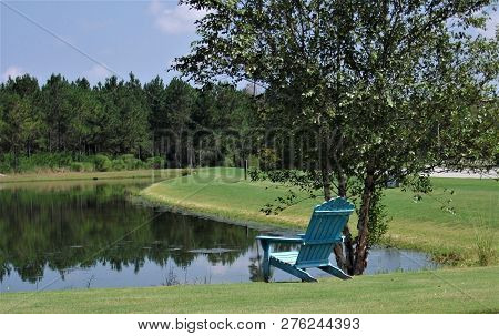 A Lone Chair Sits Beside A Lake In Florida.