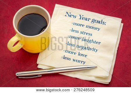 New Year goals: more money, less stress, more love, less worry ... - handwriting on a napkin with a cup of coffee