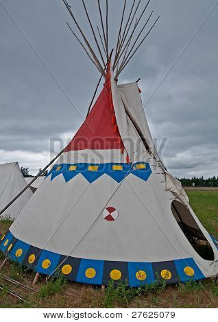 This is a traditional Native American Indian teepee set up in a vertical image against stormy cloudy skies. The doorway is ready to provide cover from the rain. poster
