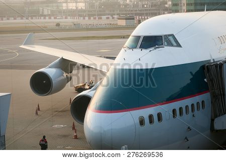 Hong Kong - Dec 2014: Cathay Pacific Boeing 747-400 Jumbo Jet Parks At The Gate In Front Of Terminal