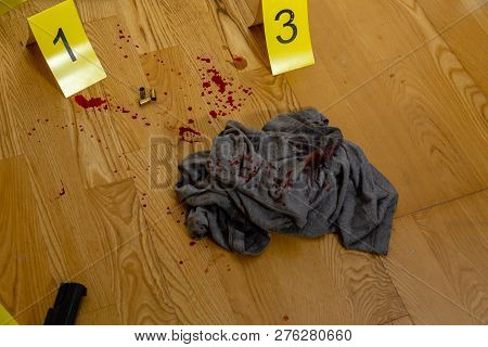 Bullets, Bloody Clothes And Gun At Crime Scene