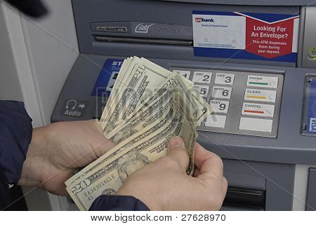USA/IDAHO STATE/ LEWISTON _ Senior female cashing money from US Bank ATM cash machines and counting dollars bills 19 Dec. 2011 (PHOTO BY DEAN PICTURES)