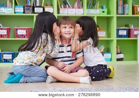 Two Girl Kids Whisper Secret At Ear Of Boy In Library At Kindergarten Preschool,fun And Happy Childr
