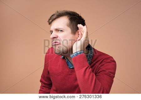 Man Bending Towards With Hand Near Ear And With Curious Look And Interest Listening Rumor