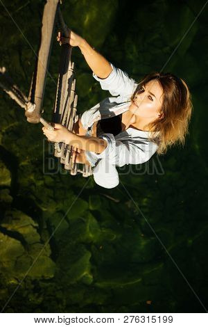 Achieving Her Towering Ambition. Sexy Woman Climbing Up Rope Ladder. Pretty Woman Climb Jacobs Ladde