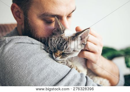Cat And Man, Portrait Of Happy Cat With Close Eyes And Young Beard Man. Handsome Young Man Is Huggin