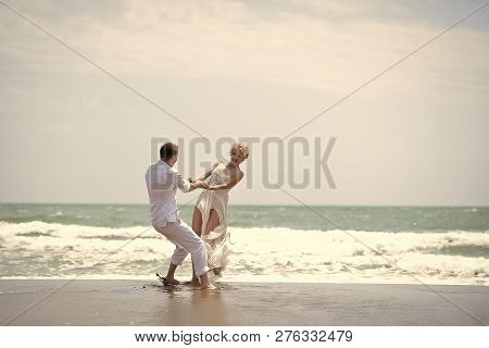 Attractive Young Happy Pair Couple Of Man And Woman In White Spinning On Ocean Beach Coast On Windy