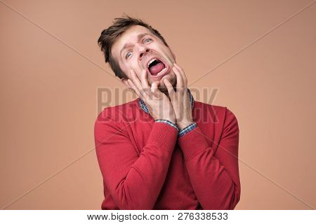 Young European Man In Red Sweater Crying Of Pain Anf Grief On Brown Background.