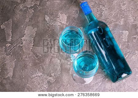 Two Glasses And Bottle Of Trendy Blue Wine. Spanish Blue Wine Chardonnay On Dark Concrete Background