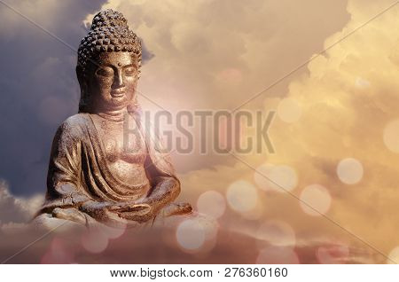 Buddha Statue Sitting In Meditation Pose Against Sunset Sky With Golden Tones Clouds.