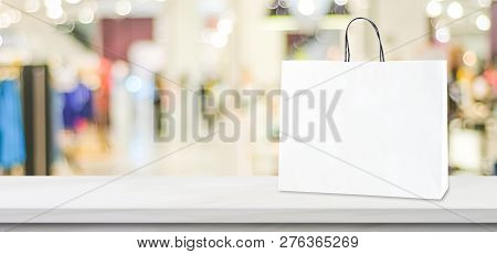 White Paper Shopping Bag Standing On White Marble  Table Over Blurred Store Background With Copy Spa