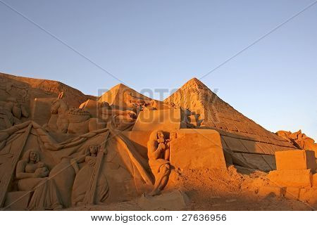 Ancient scenery in Egypt with pyramids made from sand against a blue sky