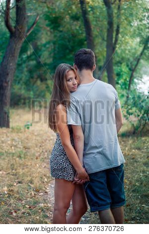 Beautiful Teen Girl Laid Her Head On The Shoulder Of The Guy Standing Back. Loving Couple In The For