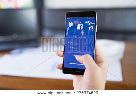 Chiang Mai, Thailand - May 06,2018: Man Holding Huawei With Facebook App On The Screen. Facebook Is