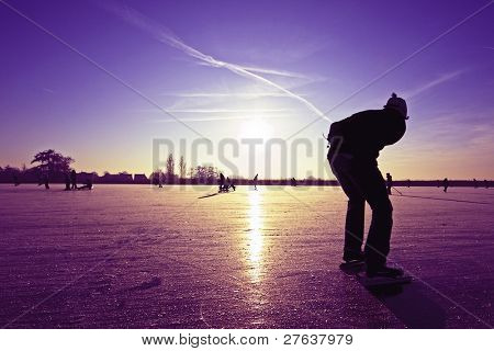 Lonely ice skater at a purple sunset on a lake in the countryside from the Netherlands