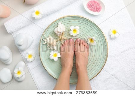 Woman soaking her feet in plate with water, flowers and seashells on white towel, top view. Spa treatment poster