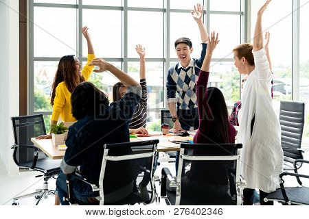 Young Multiethnic Diverse Creative Asian Group Huddle And High Five Hands Together In Office Worksho