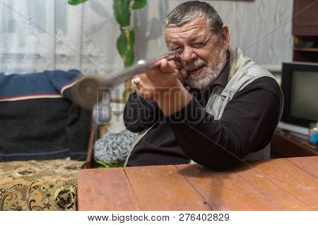 Bearded Caucasian Senior Aiming His Walking Stick Like A Gun Sitting At The Table Indoor