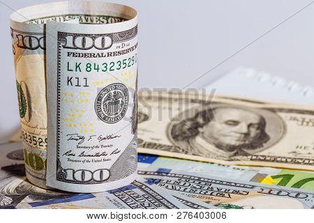 Round Curved Hundred Us Dollar Bill Standing On The Background Of Hundred Usa Dollar Banknotes, Sele