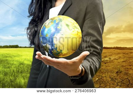 Business Woman Holding The Earth Against Climate Change Background. Global Awareness Concept