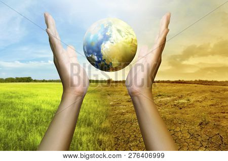 Human Hands Holding A Globe With Climate Change On The Background. Global Awareness Concept